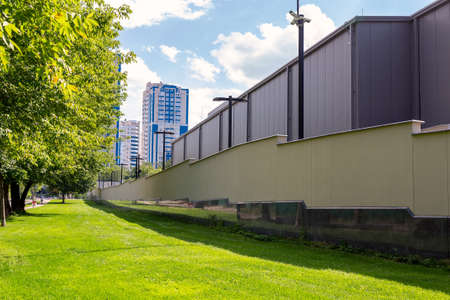 Green grass lawn and secured high fenced area with secutity cctv cameras ofresidential apartment , office of industrial building. Tall wall protected safety zone district in crime city