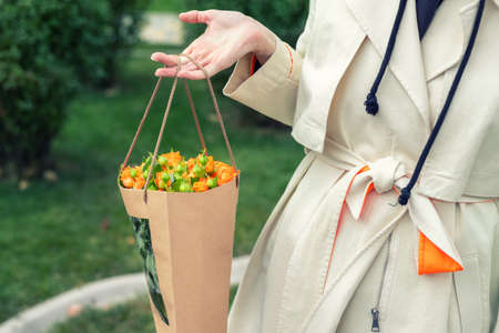 Close-up young adult fashion classy woman model hand holding authentic fresh orange spray roses flower bouquet wrapped in craft paper bag on city urban street outdoor. Spring present gift dilevery Archivio Fotografico