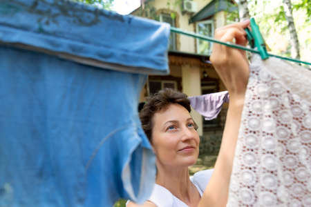 Candid real life portrait of young adult beautiful attractive caucasian woman hanging up fresh washed family clothes on birch tree clothesline with pins at home yard on bright sunny day outdoors Archivio Fotografico