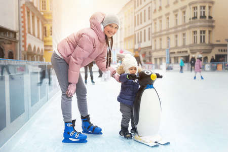 Young adult attractive beautiful caucasian woman enjoy having fun with little toddler son at outdoor skating rink while travel in old european city in winter. Mom and child holiday sport acitivities Archivio Fotografico