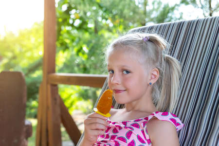 Cute adorable caucasian blond little kid girl enjoy having fun relaxing and eat mango fruit icecream sitting on sunbed in yard garden near pool sea beach. Child chilling outdoor on sunny day