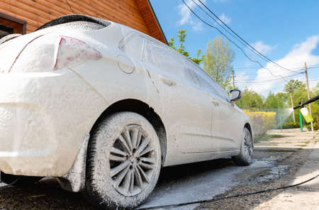 Manual car wash with high pressure water equipment pump at home backyard outdoors on bright shiny summer day. Vehicle covered with foam shampoo chemical detergents during carwash self service