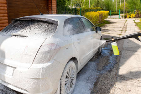 Manual unknown car wash with high pressure water equipment pump at home backyard outdoors on bright shiny summer day. Vehicle covered with foam shampoo chemical detergents during carwash self service Archivio Fotografico