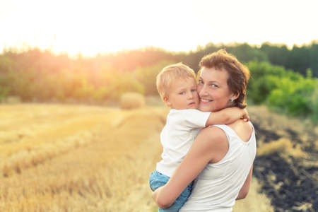 Young adult attractive beautiful mom holding on hand and hugging little son enjoy walking by golden wheat harvested field near farm. Happy child and parent on rural nature country sunset landscape Archivio Fotografico