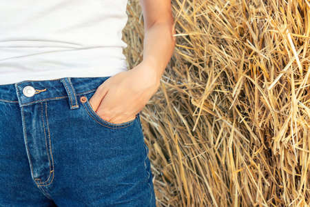 Close-up young adult woman hand in blue denim jeans pocket shorts or pants stand against hay stack at country rural barn or backyard. Detail of female arm in pants on countryside cottage farm yard