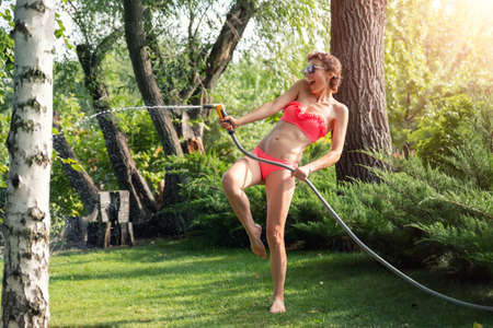 Young adult sexy slim sporty caucasian brunette woman enjoy having fun watering garden at home yard with hose pipe shower on hot summer day. Happy female person relax at backyard tree park outdoors