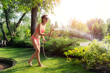 Young adult sexy slim sporty caucasian brunette woman enjoy having fun watering garden at home yard with hose pipe shower on hot summer day. Happy female person relax at backyard park outdoors
