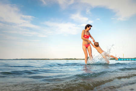 Beautiful young adult caucasian mom enjoy having fun at lake river beach spin little toddler boy son around making water splash. Family travel and vacation with children concept. Outdoor activities