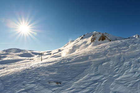 Scenic view of snow covered alpine mountain on bright sunny winter day. Snowcapped peaks against vibrant shining sun on blue clear sky. panoramic nature landscape