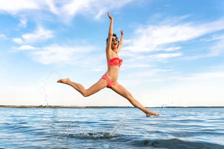 Young adult sporty slim sexy beautiful caucasian female person in bikini swimsuit and sunglasses leaping and jumping at sea or lake shore beach summer resort. Youth vacation weekend joy concept Archivio Fotografico