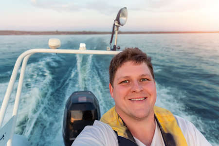 Young adult happy caucasian excited man portrait enjoy having fun driving fast motorboat on pond water surface at sunset evening time. Male person sailing fishing on speedboat by lake in morning