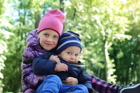 Two cute adorable playful caucasian siblings boy girl child enjoy havefun on playground at backyard or city park outdoors. Little toddler brother and sister portrait hugging and smiling. Family care Archivio Fotografico