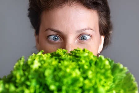 Young adult beautiful caucasian happy smiling woman portrait looking dedesire green fresh lettuce salad crop in front face. Healthy food nutrition concept. Green oraganic eco bio natural vegan meal