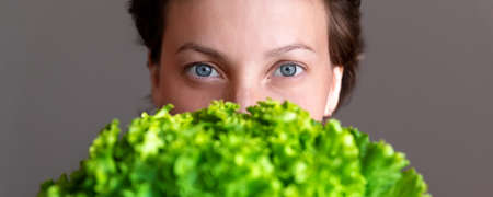 Young adult beautiful caucasian happy smiling woman portrait holding green fresh lettuce salad front face. Healthy food nutrition concept. Green oraganic eco bio natural vegan meal. Wide banner cro