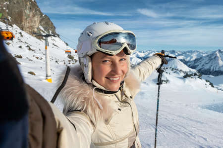 Young adult beautiful happy attractive caucasian smiling skier woman portrait making selfie on mountain peak showing skiing resort panorama breathtaking view. Winter travel adventure welcome concept.