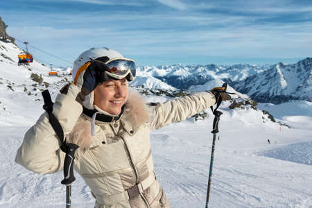 Young adult beautiful happy attractive caucasian smiling skier woman portrait teke on mask on mountain peak showing skiing resort panorama breathtaking view. Winter travel adventure welcome concept.