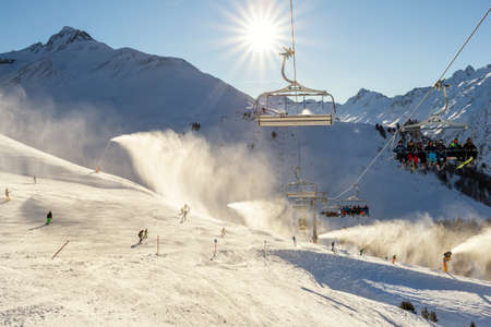 Scenic panoramic view of alpine peaks with ski lift ropeway on hilghland mountain winter resort and snow making machines on bright cold sunny day. downhill slopes with people enjoy sport activities