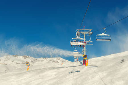 Scenic panoramic view of alpine peaks with ski lift ropeway on hilghland mountain winter resort and snow making machines on bright cold sunny day. downhill slopes with people and clear blue sky Archivio Fotografico