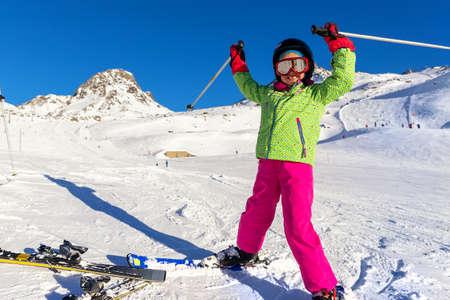 Active adorable preschooler caucasian kid girl portrait with ski in helmet, goggles and bright suit enjoy winter sport activities puh hand up. Little child skiing on luxury alpine resort in mountains