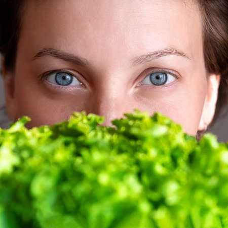 Young adult beautiful caucasian happy smiling woman portrait holding green fresh lettuce salad crop in front face. Healthy food and nutrition concept. Green oraganic eco bio natural vegan meal