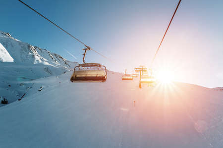 Ski lift empty ropeway on hilghland alpine mountain winter resort on bright sunny evening . Ski chairlift cable way with people enjoy skiing and snowboarding. Sunset sky backlit shining on background Standard-Bild