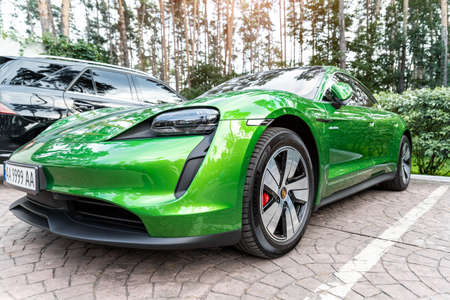 Kyiv, Ukraine - September 6th, 2020: New electric zero emission sportscar Porsche Taycan turbo in Mamba green metallic color parked on city street outdoors at forest on autumn day