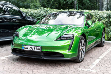 Kyiv, Ukraine - September 6th, 2020: New electric zero emission sportcar Porsche Taycan turbo in Mamba green metallic color parked on city street outdoors on autumn day