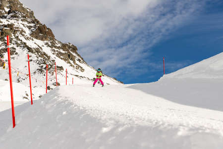 Active adorable preschooler caucasian smiling kid girlriding fast ski in helmet, goggles and bright suit enjoy winter sport activities . skiing on luxury alpine resort in mountains. Race competition