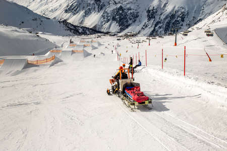 Snowmobile machine with sled and equipment riding fast hurry up driver to help injured skier or snowboarder at accident on winter mountain resort. Emergency rescue vehicle at ski slope piste downhil
