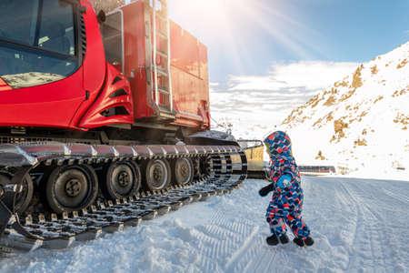 Cute adorable playful happy toddler boy play at red modern snowcat ratrack snowplow box grooming standing on peak alpine skiing resort Ischgl Austria. Heavy machinery mountain equipment track vehicle