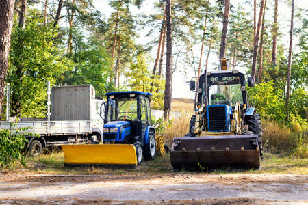 Two small and big modern tractors parked at backyard near forest farm at countryside. Residential home technic and agricultural equipment. Machinery parked for maintenance and storage outdoors Stockfoto