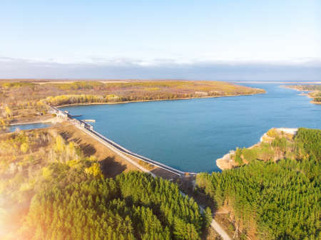 Aerial drone bird eye view of big artificial water storage reservoir on river Oskol with hydropower turbine electricity power generationplant. Natural ukrainian beautiful lake and forest landscape
