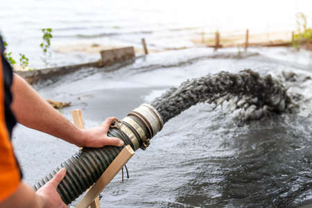 Engeneer hold pipe of power pump machine pouring mud sludge waste water with sand silt on ground. Sand-wash and coast-depeening. Septic sewage maintenance service. Industrial environment pollution