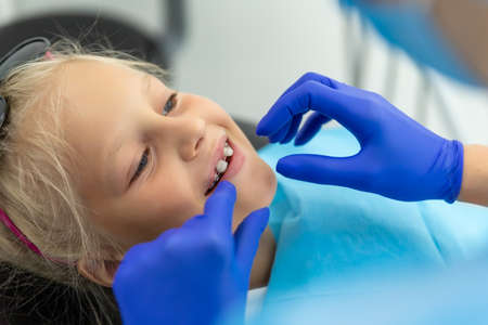 Little cute adorable happy caucasian blond kid girl at dentist office at dentist check-up of dental braces. Child during orthodontist visit and oral cavity treatment. Children tooth care and hygiene Stock Photo