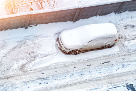 Top aerial view of apartment office building parking lot with many cars covered by snow stucked after heavy blizzard snowfall winter day. Snowdrifts and freezed vehicles. Extreme weather conditions