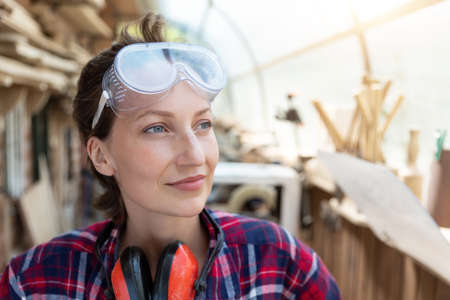 Young beautiful handy professional happy female strong carpenter portrait wearing protective goggles working in carpentry diy workshop against wood. Confident engineer. Women male hobby at workbench