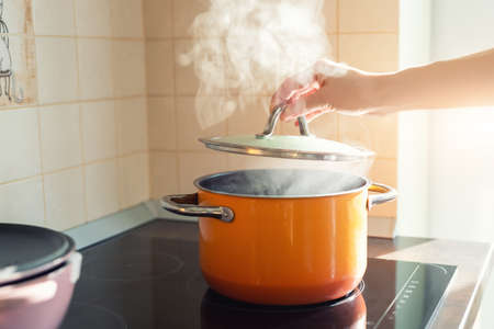 Female hand open lid of enamel steel cooking pan on electric hob with boiling water or soup and scenic vapor steam backlit by warm sunlight at kitchen. Kitchenware utensil and tool at home background Stock Photo