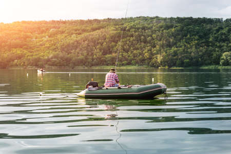 Silhouette one alone mature man sitting in green inflatable rubber motor boat and enjoy relax fishing on foggy overcast morning against forest shore. Calmness tranquil freedom hobby scene concept Stockfoto