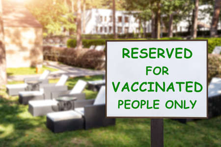 Text plate RESERVED FOR VACCINATED PEOPLE ONLY at luxury hotel pool beach resort area empty loungers on summer day. New normal travel and vacation concept. Covid-19 pandemic restriction and limit