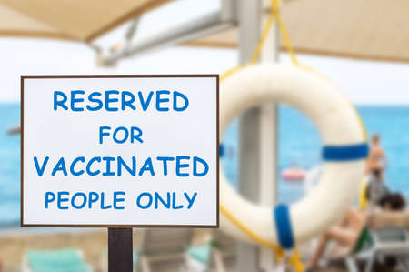 Text plate RESERVED FOR VACCINATED PEOPLE ONLY at luxury hotel sea beach resort area empty loungers on summer day. New normal travel and vacation concept. Covid-19 pandemic restriction and limit