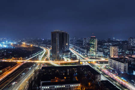 Aerial panoramic drone above roof view of Kiev night traffic road junction scene. Highway city at evening car light trails. Scenic urban skyline cityscape. Busy downtown life of Ukraine capital