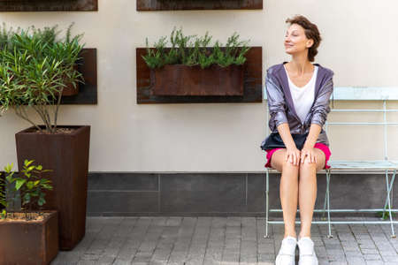 Young adult beautiful caucasian woman sitting on metal vintage bench chair against wall with many mounted ruty plant pot on city street. Attractive female person waiting meeting outdoors in garden