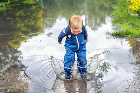 Little cute playful caucasian blond toddler boy enjoy have fun playing jumping in dirty puddle wearing blue waterproof pants and rubber rainboots at home yard street outdoor. Happy childhood concept Stockfoto