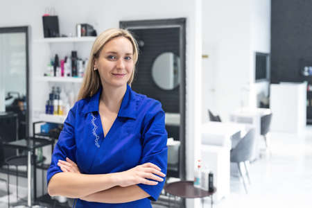Young attractive confident professional beautician doctor portrait in blue uniform at beauty clinic salon. Cosmetologist specialist doing skincare treatment .Health care therapy Stockfoto