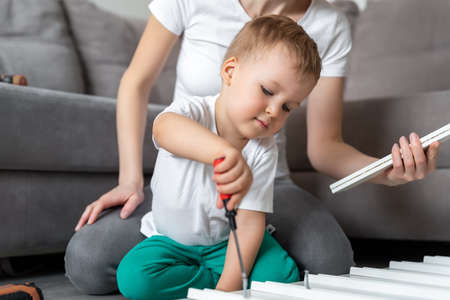 Cute adorable concentrated caucasian toddler boy kid sit on floor and help mom assembling furniture shelf with screwdriver. Young adult mum with funny little child enjoy playing at home indoors Stockfoto