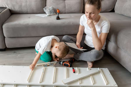 Cute adorable caucasian toddler boy kid sit on floor and help mom assembling furniture shelf with power screwdriver tool. Young adult incomrehensive woman reading instruction manual furniture indoor