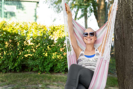 Young adult happy short haired shaved bald attractive woman chilling enjoy relaxing sitting in fabric chair hammock at yard in garden near house. Peaceful and idyllic outdoor rest lifestyle