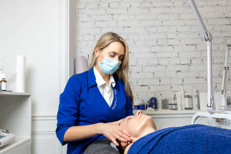 Young adult attractive professional beautician doctor portrait in protective face mask do facial care and treatment procedure to female client. Health safety therapy. Beauty salon new normal covid-19