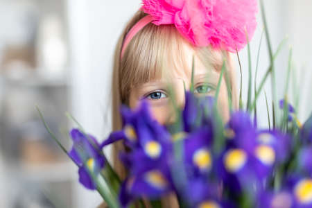 Little cute adorable blond caucasian female child girl portrait with beautiful blue eyes holding fresh purple iris flower bouquet. Happy kid face between bunch of blossoming plants. Spring concept