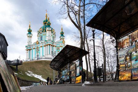 Kiev, Ukraine - March 6th, 2021: Beautiful scenic view of Saint Andrew s Church against blue sky on bright spring day in Kiev old city center. Ukrainian capital Kiyv famous podol sightseeing landmark